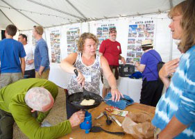 """Chris Young, or """"Yuma"""" (red shirt) watches as Mountaineering alumni prepare a feast worthy of a campout during the 60th Reunion in August."""