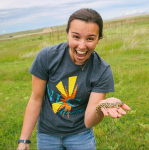 Tia holds a salamander that emerged from a prairie dog hole while cleaning up the painting project.